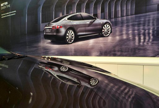 (AP Photo/Richard Vogel). An image of a Tesla model X is seen reflected on the hood of a new model 3 in the Tesla showroom in Santa Monica, Calif., on Wednesday, Aug. 8, 2018. Board members at Tesla are evaluating CEO and Chairman Elon Musk's $72 billi...