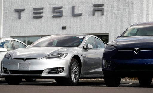 (AP Photo/David Zalubowski). In this July 8, 2018, photo, 2018 Model 3 sedan sits next to a Model X on display outside a Tesla showroom in Littleton, Colo. Board members at Tesla are evaluating CEO and Chairman Elon Musk's $72 billion proposal to take ...