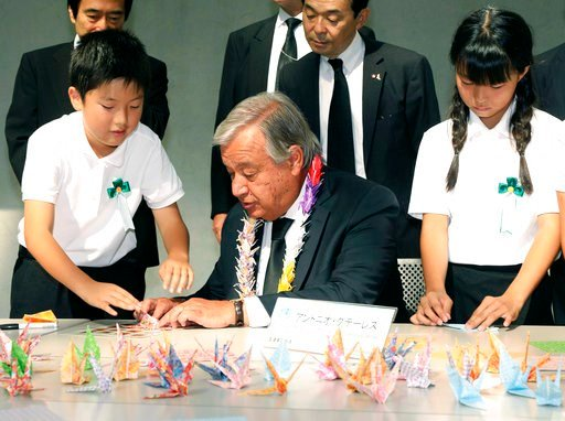 (Tatsumi Oita/Kyodo News via AP). United Nations Secretary-General Antonio Guterres, center, helped by local primary schoolchildren, folds a paper crane at Atomic Bomb Museum in Nagasaki, southern Japan, Thursday, Aug. 9, 2018, marking the 73rd anniver...