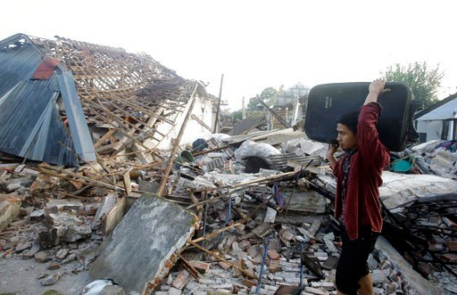 (AP Photo/Firdia Lisnawati). A man carries his belongings past the ruin of houses at a village affected by an earthquake in North Lombok, Indonesia, Thursday, Aug. 9, 2018. The north of Lombok was devastated by the powerful quake that struck Sunday nig...