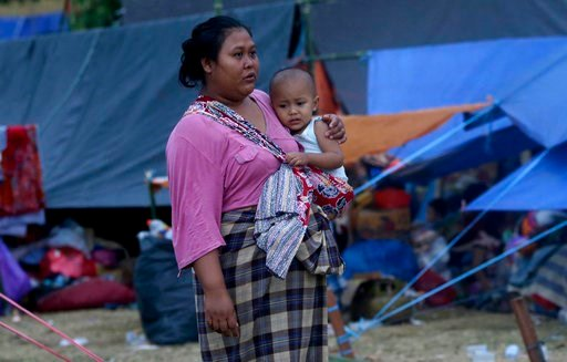 (AP Photo/Tatan Syuflana). A woman carries her child at a temporary shelter after being displaced by Sunday's earthquake in North Lombok, Indonesia, Wednesday, Aug. 8, 2018. Aid has begun reaching isolated areas of the Indonesian island struggling afte...