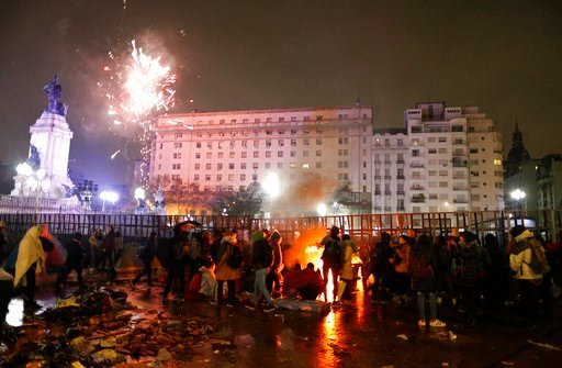 (AP Photo/Natacha Pisarenko). Pro-choice activists gather around a bonfire to keep warm as celebratory fireworks go off in the distance from a gathering of pro-life activists, as they all wait outside Congress for lawmakers to vote on an abortion bill ...