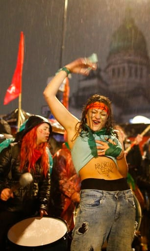 """(AP Photo/Natacha Pisarenko). A women in support of decriminalizing abortion shows the Spanish message """"Legal abortion"""" on her stomach as she gathers with others in the rain outside Congress where lawmakers are debating the issue, in Buenos Aires, Arge..."""