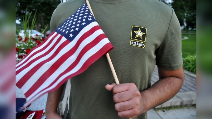 In this July 3, 2018, file photo, a Pakistani recruit, 22, who was recently discharged from the U.S. Army, holds an American flag as he poses for a picture. (Source: AP Photo/Mike Knaak, File)