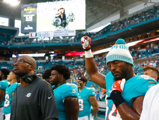 (AP Photo/Wilfredo Lee). Miami Dolphins defensive end Robert Quinn (94) raises his right fist during the singing of the national anthem, before the team's NFL preseason football game against the Tampa Bay Buccaneers, Thursday, Aug. 9, 2018, in Miami Ga...