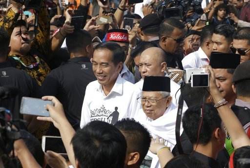 """(AP Photo/Tatan Syuflana). Indonesian President Joko """"Jokowi"""" Widodo, center left, and his running mate Ma'ruf Amin, center right, greet their supporters prior to formal registration as candidates for the 2019 presidential election in Jakarta, Indonesi..."""