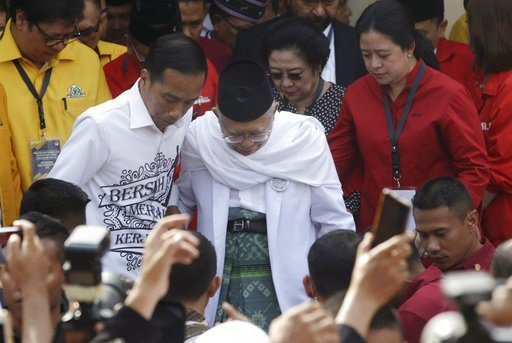 """(AP Photo/Tatan Syuflana). Indonesian President Joko """"Jokowi"""" Widodo, center left, and his running mate Ma'ruf Amin, center right, walk together prior to formal registration as candidates for the 2019 presidential election in Jakarta, Indonesia. Friday..."""