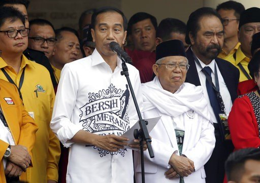"""(AP Photo/Tatan Syuflana). Indonesian President Joko """"Jokowi"""" Widodo, center left, speaks as his running mate Ma'ruf Amin, center right, listens prior to formal registration as candidates for the 2019 presidential election in Jakarta, Indonesia. Friday..."""