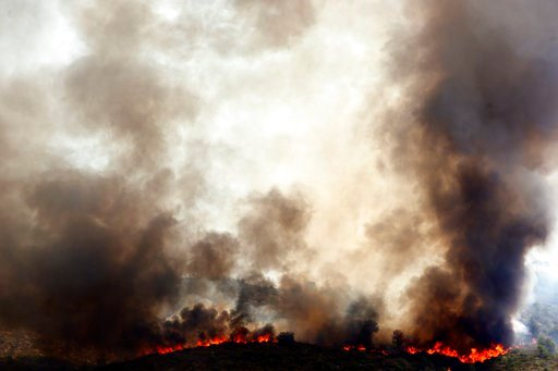 (AP Photo/Alberto Saiz). Spanish firefighters try to extinguish a wildfire in Pinet village, near Valencia Tuesday, Aug. 7, 2018. Spanish firefighters are still working to bring under control a forest blaze near Valencia.