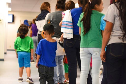 (Charles Reed/U.S. Immigration and Customs Enforcement via AP). In this Thursday, Aug. 9, 2018, photo, provided by U.S. Immigration and Customs Enforcement, mothers and their children stand in line at South Texas Family Residential Center in Dilley, Te...