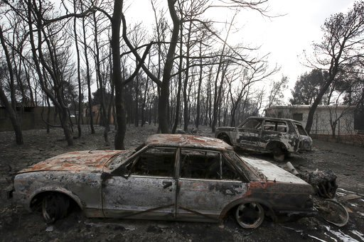 (AP Photo/Thanassis Stavrakis, FILE). FILE - In this file photo dated Tuesday, July 24, 2018, burned cars are seen outside a damaged house in Rafina, east of Athens, after wildfires raged through the holiday resorts near Greece's capital.  The prime mi...