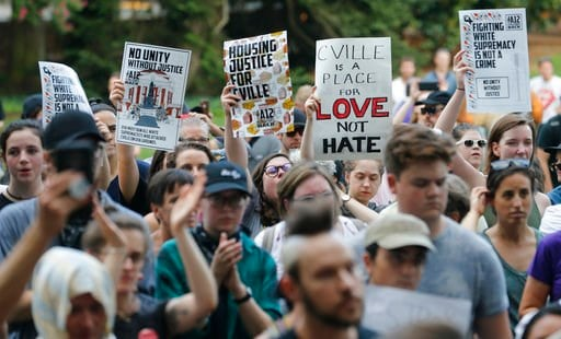(AP Photo/Steve Helber). Demonstrators march on the campus of the University of Virginia in anticipation of the anniversary of last year's Unite the Right rally in Charlottesville, Va., Saturday, Aug. 11, 2018.