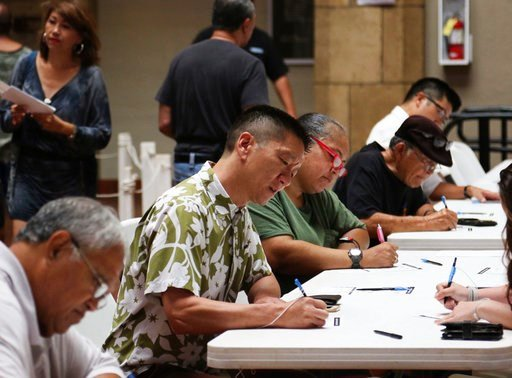 (AP Photo/Jennifer Sinco Kelleher). Congressional candidate Lt. Gov. Doug Chin, center, signs in to vote at an early polling location in Honolulu on Thursday, Aug. 9, 2018. Hawaii's weekend primary election will most likely settle the outcome of this y...