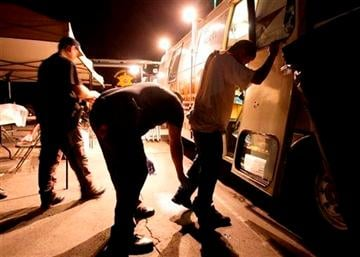 (AP Photo/Ross D. Franklin, File). FILE - In this July 29, 2010 file photo, Maricopa County Sheriff's deputies, left, check the shoes of a suspect arrested during a crime suppression sweep in Phoenix.