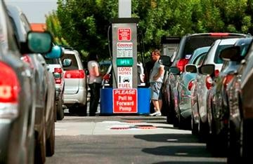 (AP Photo/Damian Dovarganes). Costco members fill up with discounted gasoline at a Costco gas station in Van Nuys, Calif., Friday, Oct. 5, 2012.