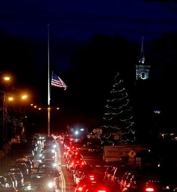 (AP Photo/Seth Wenig). Under a flag at half-staff and a Christmas tree, traffic piles up along a main road in Newtown, Conn., Thursday, Dec. 20, 2012.