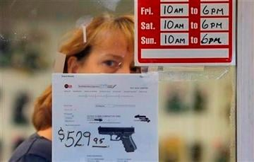 (AP Photo/Elaine Thompson). FILE - In this Wednesday, Dec. 19, 2012 file photo, a clerk peers out from a gun shop in Seattle.