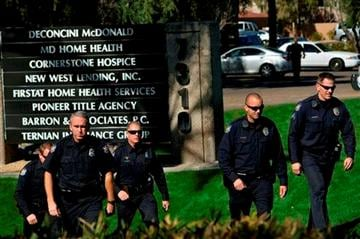 (AP Photo/Patrick Sison). Police officers leave an office building after a shooting at the building in Phoenix on Wednesday, Jan. 30, 2013.