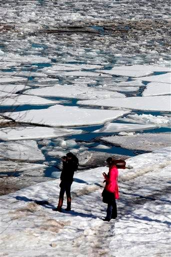 (AP Photo/Kiichiro Sato). Visitors take pictures of an ice filled Chicago River Wednesday, Feb. 19, 2014, in downtown Chicago.