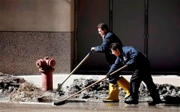 (AP Photo/Kiichiro Sato). Workers at a downtown parking garage removes snow melt water to the storm drain Wednesday, Feb. 19, 2014, in Chicago.