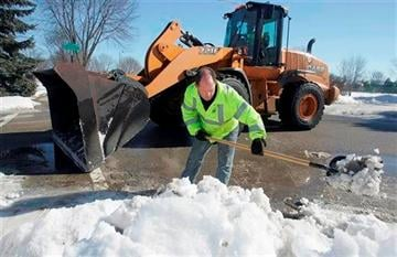 (AP Photo/Northwest Herald, H. Rick Bamman). Supervisor of Streets Jim Veugeler clears snow from a storm drain as maintenance worker Dave Shine operates a front end loader in Crystal Lake, Ill., Wednesday, Feb 18, 2014.