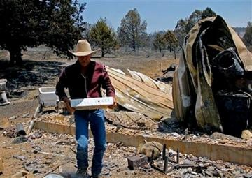 (AP Photo/The Herald and News, Lacey Jarrell). Sprague River, Ore., resident David Pool lifts a marble block from the rubble left by the Moccasin Fire, Tuesday, July 15, 2014.