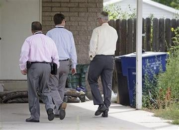 (AP Photo/Rick Bowmer). Police walk near garbage cans where a baby was found Tuesday, Aug. 26, 2014, in Kearns, Utah.