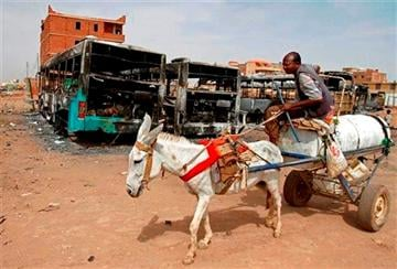 (AP Photo/Abd Raouf, File). FILE - In this Thursday, Sept. 26, 2013 file photo, a man on a donkey cart passes burned buses following rioting and unrest in Khartoum.