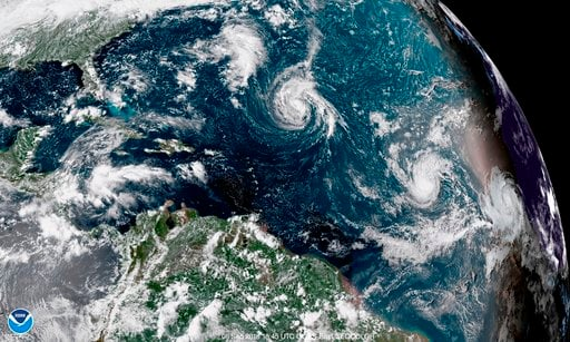 (NOAA via AP). This enhanced satellite image made available by NOAA shows Tropical Storm Florence, center, in the Atlantic Ocean on Saturday, Sept. 8, 2018 at 2:45 p.m. EDT.