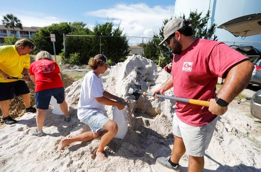(AP Photo/Mic Smith). Walker Townsend, at right, from the Isle of Palms, S.C., fills a sand bag while Dalton Trout, in center, holds the bag at the Isle of Palms municipal lot where the city was giving away free sand in preparation for Hurricane Florence.