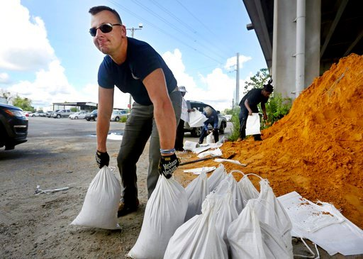 (Grace Beahm Alford/The Post And Courier via AP). Kevin Orth loads sandbags into cars on Milford Street as he helps residents prepare for Hurricane Florence, Monday, Sept. 10, 2018, in Charleston, S.C.