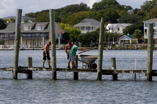 (AP Photo/Tom Copeland). From left, Josh Clappsy, Blake Price, and JB Phillips remove boards from a dock in hopes to save it from rising waters in Swansboro, N.C., Tuesday, Sept. 11, 2018. Florence exploded into a potentially catastrophic hurricane Mon...