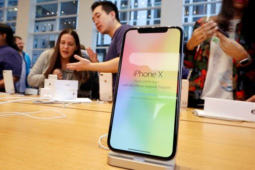 (AP Photo/Richard Drew, File). In this Nov. 3, 2017, file photo, customers buy the iPhone X at the Apple Store on New York's Fifth Avenue.
