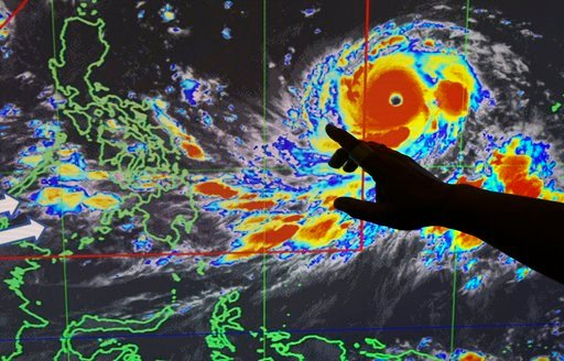 "(AP Photo/Aaron Favila). Filipino forecaster Meno Mendoza illustrates the path of Typhoon Mangkhut, locally named ""Typhoon Ompong"" as it approaches the Philippines with sustained winds of 205 kilometers per hour (127 miles per hour) and gusts of up to ..."