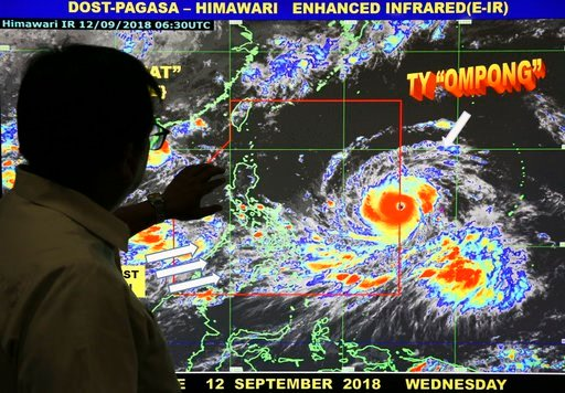"(AP Photo/Aaron Favila). Filipino forecaster Meno Mendoza shows the path of Typhoon Mangkhut, locally named ""Typhoon Ompong"" as it approaches the Philippines with sustained winds of 205 kilometers per hour (127 miles per hour) and gusts of up to 255 kp..."