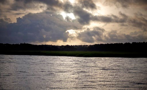 (AP Photo/David Goldman, File). FILE - In this June 10, 2013, file photo, the sun rises over Sapelo Island, Ga., a Gullah-Geechee community. A tight-knit community of slave descendants on the South Carolina coast is used to riding out big storms, from ...