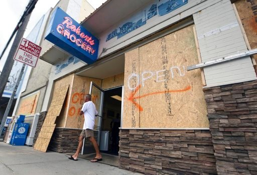 (Matt Born/The Star-News via AP, File). FILE- In this Tuesday, Sept. 11, 2018, file photo a man walks out of the boarded up Robert's Grocery in Wrightsville Beach, N.C., in preparation for Hurricane Florence. Though it's far from clear how much economi...