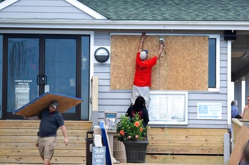 (Matt Born/The Star-News via AP, File). FILE- In this Tuesday, Sept. 11, 2018, photo crews board up the Oceanic restaurant in Wrightsville Beach, N.C., in preparation for Hurricane Florence. Though it's far from clear how much economic havoc Hurricane ...