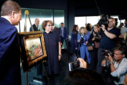 "(AP Photo/Mark Lennihan). United States Attorney Geoffrey Berman, left, unveils a Renoir painting with Sylvie Sulitzer at a news conference, Wednesday, Sept. 12, 2018, in New York. The 1919 oil painting ""Femmes Dans Un Jardin"" was seized in Paris by th..."