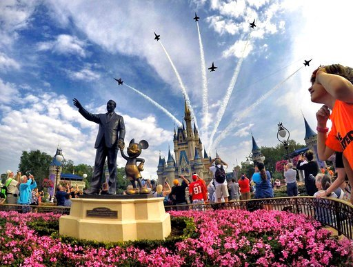 (Joe Burbank/Orlando Sentinel via AP, File). FILE- In this April 16, 2017 file photo, the Blue Angels, the U.S. Navy's legendary flight performance squadron, fly in formation over Cinderella Castle and the 'Partners' statue at the Magic Kingdom at Walt...