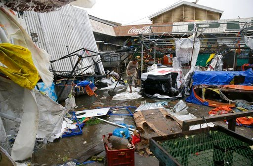 (AP Photo/Aaron Favila). Residents walk along destroyed stalls at a public market due to strong winds as Typhoon Mangkhut barreled across Tuguegrao city in Cagayan province, northeastern Philippines on Saturday, Sept. 15, 2018. The typhoon slammed into...