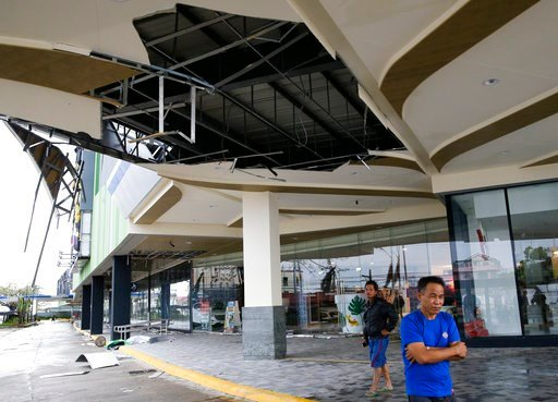 (AP Photo/Aaron Favila). Residents stand beside a damaged portion of a mall due to strong winds from Typhoon Mangkhut as it barreled across Tuguegarao city in Cagayan province, northeastern Philippines on Saturday, Sept. 15, 2018. The typhoon slammed i...