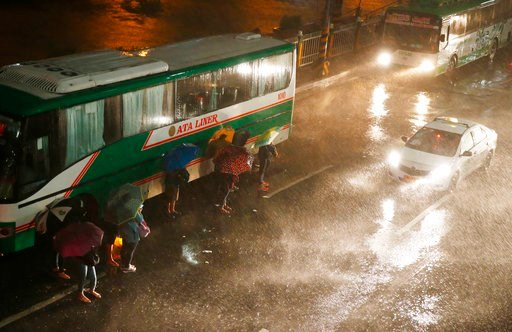 (AP Photo/Bullit Marquez). Commuters brave the rain and strong winds brought about by Typhoon Mangkhut which barrelled into northeastern Philippines before dawn Saturday, Sept. 15, 2018, in Manila, Philippines. Typhoon Mangkhut, the strongest typhoon t...