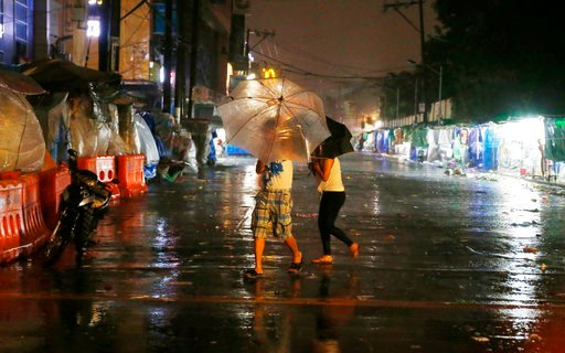 (AP Photo/Bullit Marquez). Commuters brave the rain and strong winds brought about by Typhoon Mangkhut which barrelled into northeastern Philippines before dawn Saturday, Sept. 15, 2018, in Manila, Philippines.  Typhoon Mangkhut, the strongest typhoon ...