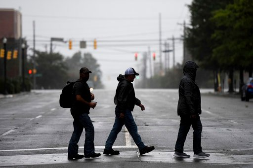 (AP Photo/Sean Rayford). People cross a downtown street in Columbia, S.C. as the remnants of Hurricane Florence slowly move across the East Coast Saturday, Sept. 15, 2018.