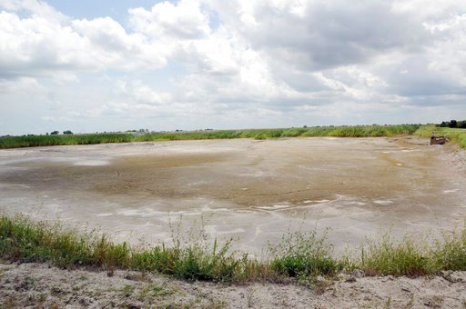 (Mike Spencer/The Star-News via AP). FILE - In this June 23, 2014 file photo, the dried-up bed of an inactive coal ash pond is seen at Duke Energy's Sutton plant in Wilmington, N.C. Duke Energy says heavy rains from Florence have caused a slope to coll...