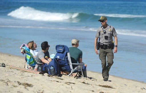 (Merrily Cassidy/The Cape Cod Times via AP). Cape Cod National Seashore Park Ranger Eric Trudeau walks up to a group of visitors on Newcomb Hollow Beach telling them that the beach is closed to swimming, Saturday, Sept. 15, 2018, in Wellfleet, Mass. Tr...