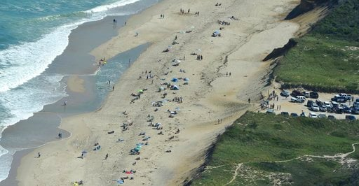 (Steve Heaslip/The Cape Cod Times via AP). Police and rescue vehicles fill the parking lot at Newcomb Hollow Beach in Wellfleet, Mass., Saturday, Sept. 15, 2018, after a man was fatally attacked by a shark.