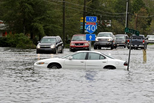 (AP Photo/Chuck Burton). Cars try to navigate a flooded road leading to Interstate 40 in Castle Hayne, N.C., after damage from Hurricane Florence cut off access to Wilmington, N.C., Sunday, Sept. 16, 2018.