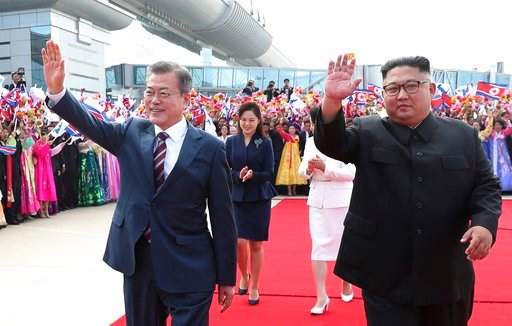 (Pyongyang Press Corps Pool via AP). South Korean President Moon Jae-in and North Korean leader Kim Jong Un, right, wave during a welcoming ceremony at Sunan International Airport in Pyongyang in North Korea, Tuesday, Sept. 18, 2018.